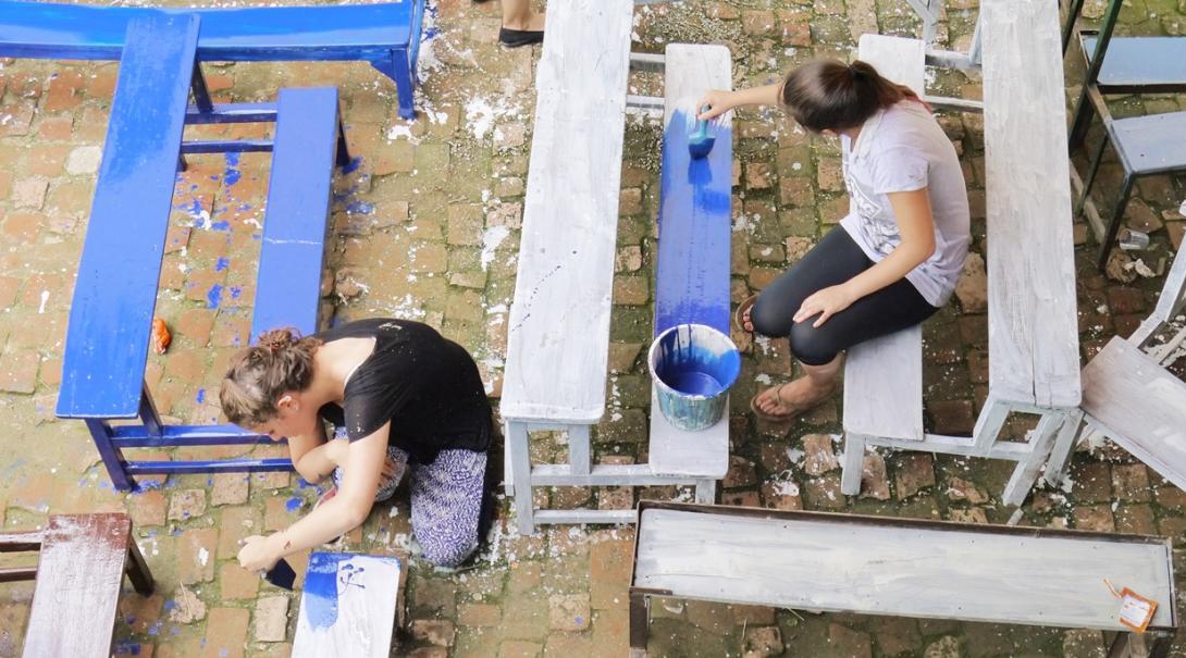 ネパールで教育施設のベンチの塗装作業に取り組むチャイルドケアボランティアたち